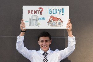 Man holding a sign that talks about renting versus buying a home