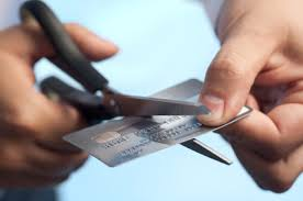 Man cutting up his credit cards in order to stay out of debt