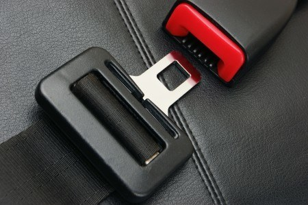 A seat belt being buckled. Driving safely goes a long way in avoiding accidents.