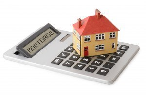 Mortgage calculator with a small home sitting on top of it signifying how to calculate a home mortgage payment