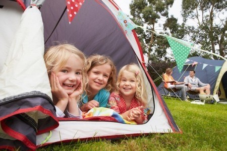 3 kids looking out a tent while camping