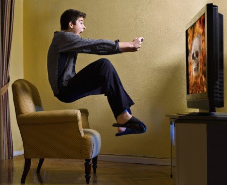 Man playing a video game jumping off a chair